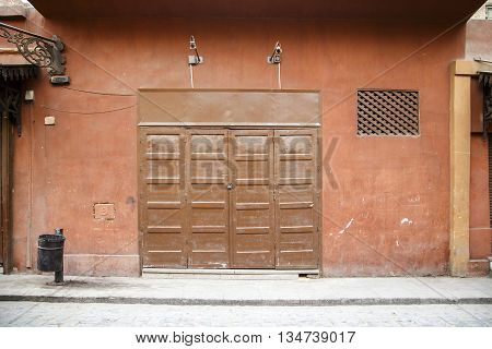 Folding door closed. wooden door closed, small shop.