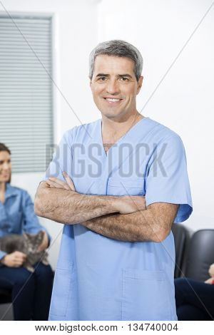 Confident Nurse With Arms Crossed Standing In Clinic