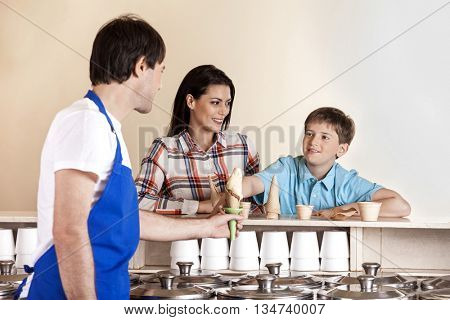 Boy Receiving Ice Cream From Waiter While Standing By Mother