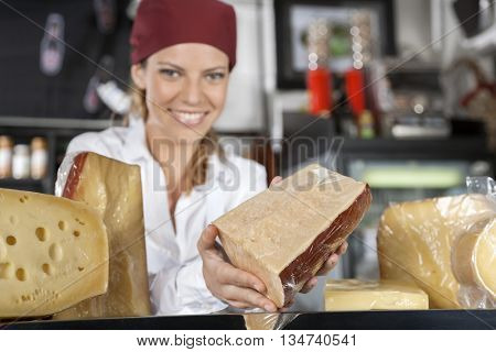 Saleswoman Showing Cheese In Grocery Store