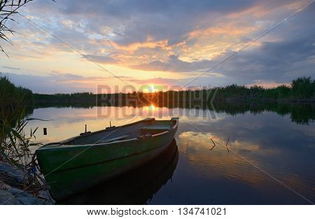 fisherman boat at sunset in summer time