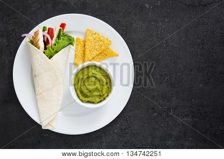 Mexican chicken fajitas with peppers lettuce and onion on a plate and slate background