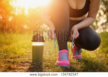 Green Detox Smoothie Cup And Woman Lacing Running Shoes Before Workout. Fitness And Healthy Lifestyl