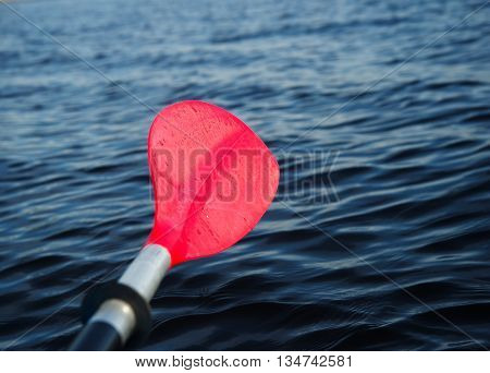 red paddle or oar of boat with dark lake background