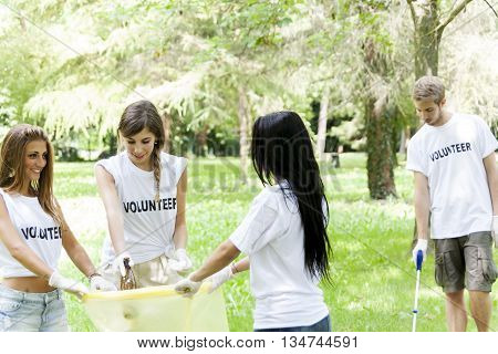 Group Of Young Volunteers Picking Up Litter In The Park