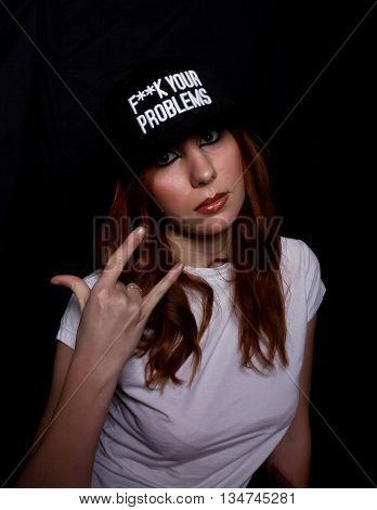 young teenager girl in a white shirt and black cap, shoots himself to the head with two fingers. play of light and shadows.