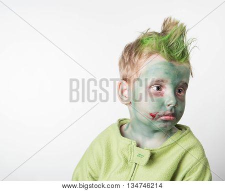 Sad little boy dressed as a zombie on halloween