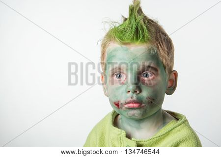 Calm little boy dressed as a zombie on halloween