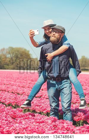 Loving couple taking photos in blooming pink tulips field in the Netherlands