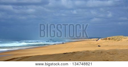 Horizontal landscape of the beach with a fisherman, shipwreck in the background and dramatic clouds (Stockton Beach, NSW, Australia)