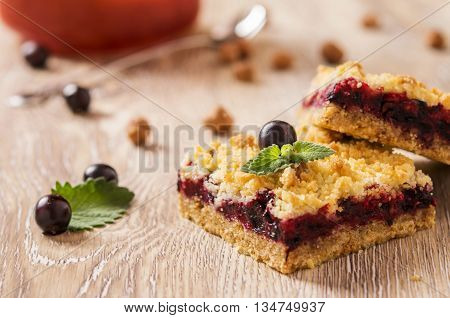 Honeysuckle crumb cake cut into square pieces on a light wooden background with berries and nuts