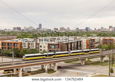 View of Dallas downtown district with yellow passenger train in foreground. Texas United States