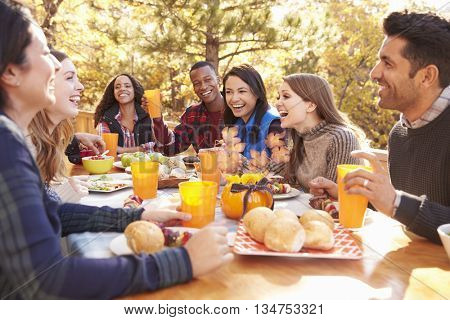 Group of happy friends eat and laugh at a table at a barbecue