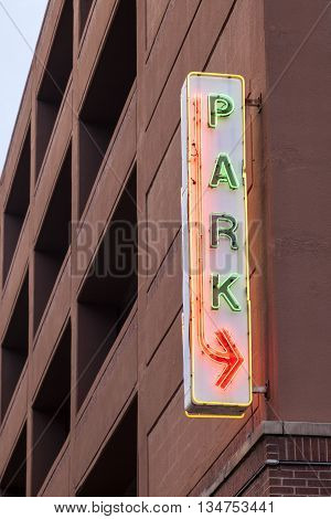 Car park parking sign illuminated at dusk
