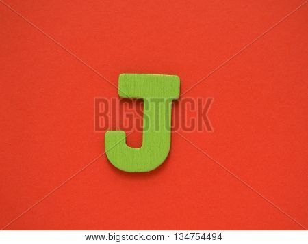 Capital letter J. Green letter J from wood on red background.
