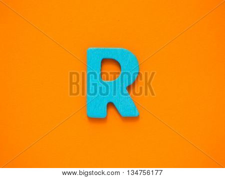 Capital letter R. Blue letter R from wood on orange background.