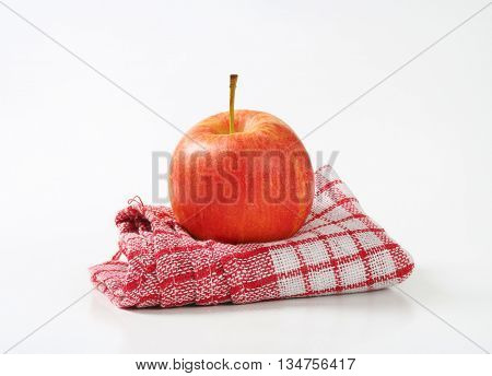 red ripe apple on checkered dishtowel