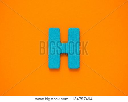 Capital letter H. Blue letter H from wood on orange background.