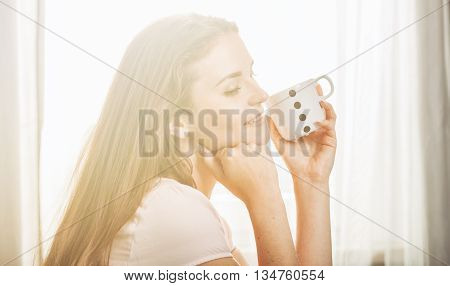 Portrait Of Young Woman Relaxing At Home And Drinking Coffee. Ca