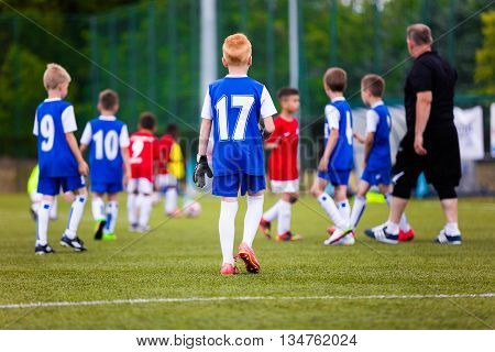 Football soccer match game for children. Youth sports team with soccer coach during football match at the stadium.