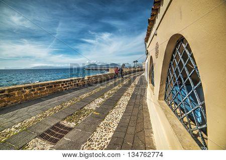 couple walking in Alghero promenade in Italy