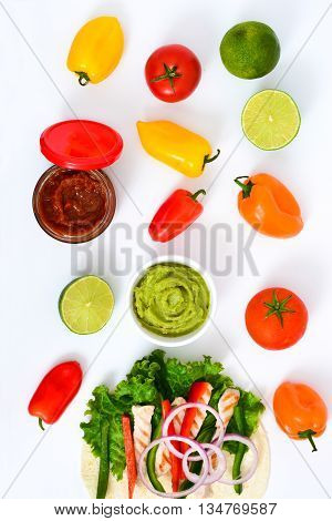 Mexican chicken fajita ingredients with peppers lettuce and onion on white background