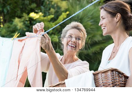 Older mother and young daughter hanging clothes outdoor to dry. Smiling daughter helping mother with laundry. Cheerful mother and daughter in conversation while hanging clothes outside.