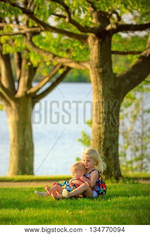 two cute caucasian sisters sitting outside in park by lake in springtime