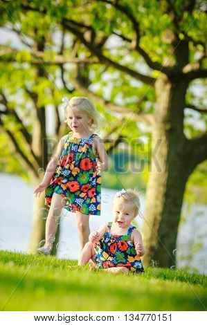 sisters playing outside in park by lake wearing matching outfits beautiful dresses