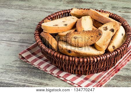 Rusks in a wicker basket on a napkin on a wooden background.