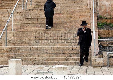 Jerusalem, Israel - March 24, 2011: Orthodox jew  walks down the stairs near Western Wall in Jerusalem Old City