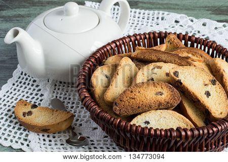 Rusks in basket, teapot and tea spoon on white openwork napkin.