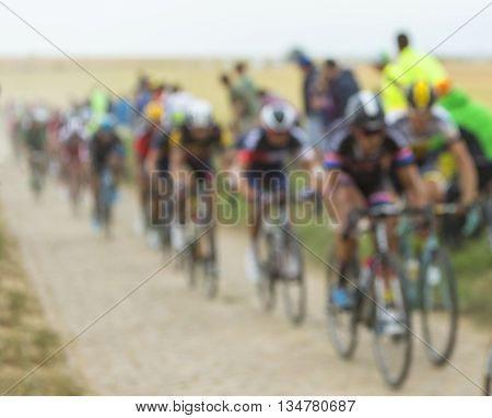 Quievy, France - July 07 2015: Out of focus image of the peloton riding on a cobblestoned road during the stage 4 of Le Tour de France 2015 in Quievy France on 07 July2015.