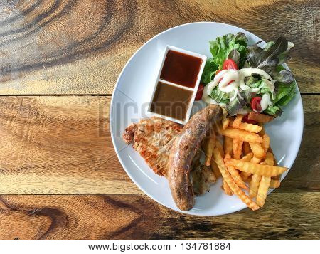 Plate Of Pork Chop Steak And Barbeque Bbq Sausage With Salaad, Fries, Pepper And Bbq Sauces On Rusti