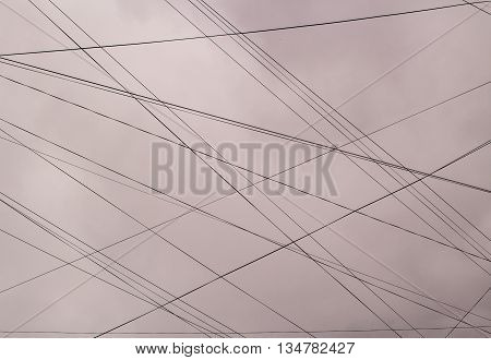 Plurality of electrical wire against the blue sky with clouds.