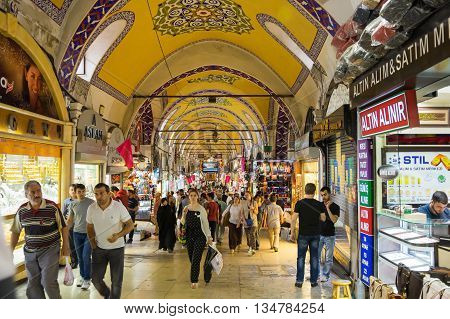 ISTANBUL TURKEY - JUNE 19 2015: Tourists visiting the Grand Bazaar in Istanbul Turkey. The Grand Bazaar is the oldest and the largest covered market in the world with 61 covered streets and over 3000 shops.