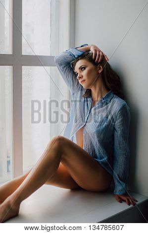 Young Pretty Woman Sitting At Window And Looking Outside Enjoys Of Rest, Wearing Blue Shirt. Studio