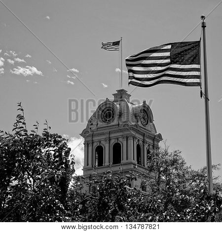 An American flag flies atop the Crook County Courthouse in Prineville, Oregon while a second one rises up from the courtyard.