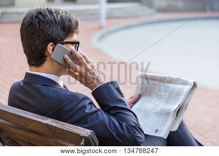 Young handsome businessman sitting on outdoor bench holding newspaper and talking on phone