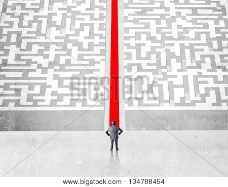 Success concept with businessman and red path groing through maze on concrete ground