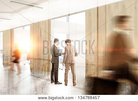 Two businessmen discussing contract in office interior. New York city background with sunlight. Double exposure