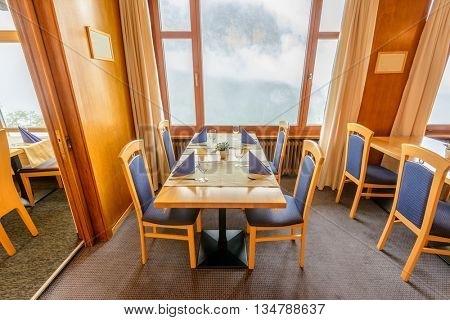 Modern dining room in luxury restaurant with fantastic swiss alps mountain view.