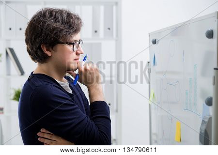 Side view of attractive young man with marker in hand analyzing business charts drawn on office whiteboard