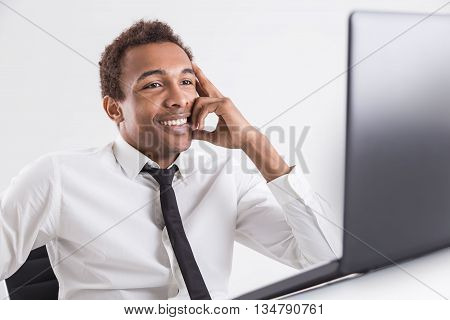 Smiling african american businessman with tie sitting at office desktop using laptop