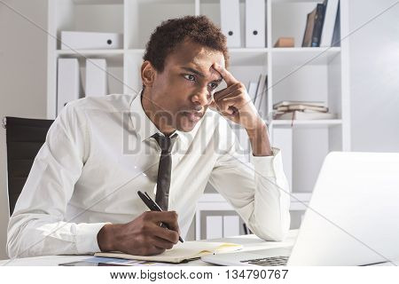 Grumpy african american businessman working on project at office desk with laptop notepad and smartphone. Shelf with documents in the background