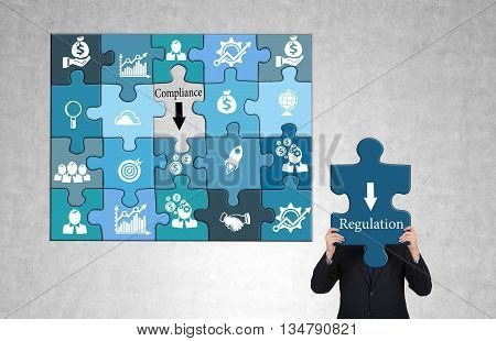 Regulation and compliance concept with business icon puzzles and businessman on concrete background