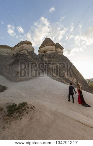 NEVSEHIR, TURKEY - APRIL 7, 2016: A young couple climbs up the rock formations in Cappadocia, Turkey