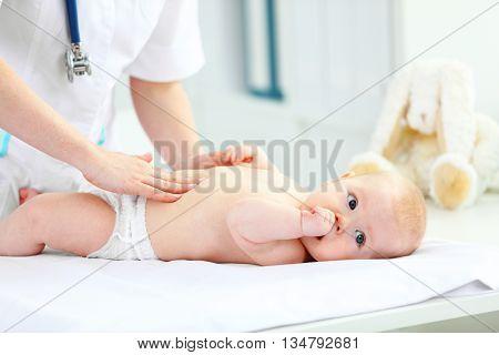 a Doctor pediatrician examines the baby tummy