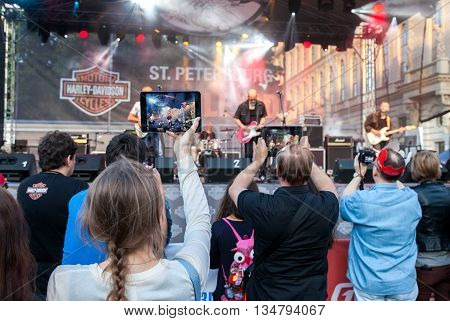 SAINT PETERSBURG RUSSIA - AUGUST 7 2015: Spectators shooting a concert rock band on your mobile devices