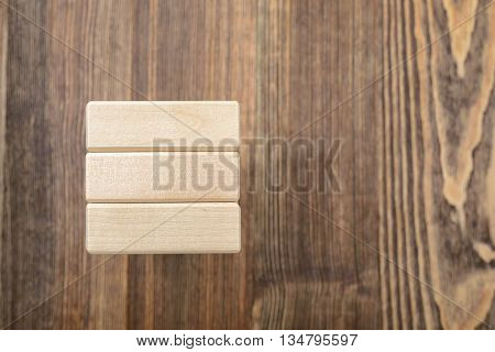 Topview of the tower of wooden blocks placed on a table. Removing blocks from a tower. Keeping balance. Full concentration. Entertainment activity. Game of physical and mental skill. Close-up photo.